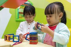 Asian Chinese little girls playing colorful magnet plastic block. S kit at indoor playground Stock Photo