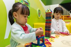 Asian Chinese little girls playing colorful magnet plastic block. S kit at indoor playground Royalty Free Stock Photos