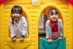 Asian Chinese little girls playing in toy house Stock Image