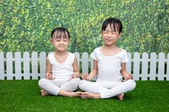 Asian Chinese little girls practicing yoga pose on a mat. Outdoor royalty free stock photography