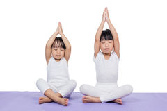 Asian Chinese little girls practicing yoga pose. On a mat indoor stock photography