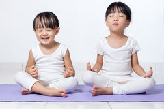 Asian Chinese little girls practicing yoga pose. On a mat indoor royalty free stock photo