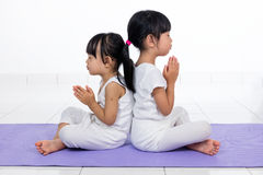 Asian Chinese little girls practicing yoga pose. On a mat indoor stock image