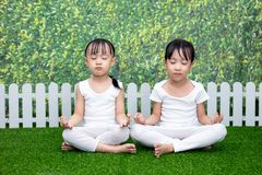 Asian Chinese little girls practicing yoga pose on a mat. Outdoor royalty free stock photo