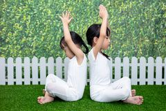 Asian Chinese little girls practicing yoga pose on a mat. Outdoor stock photos