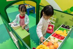Asian Chinese little girls role-playing at fruits store. At indoor playground Stock Photo