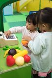 Asian Chinese little girls role-playing at fruits store. At indoor playground Royalty Free Stock Photo