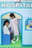 Asian Chinese little girls role-playing at hospital. At indoor playground Royalty Free Stock Photo