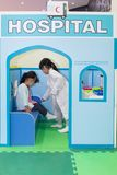 Asian Chinese little girls role-playing at hospital. At indoor playground Stock Images