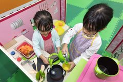 Asian Chinese little girls role-playing at kitchen. At indoor playground Stock Photography