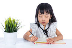 Asian Chinese little office lady writing book on the desk Royalty Free Stock Photo