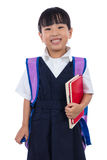 Asian Chinese little primary school girl holding books with bag Royalty Free Stock Image