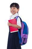 Asian Chinese little primary school girl holding books with bag Stock Image
