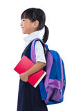 Asian Chinese little primary school girl holding books with bag Stock Photos