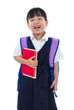 Asian Chinese little primary school girl holding books with bag. Happy Asian Chinese little primary school girl holding books with school bag in isolated white Stock Image