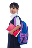 Asian Chinese little primary school girl holding books with bag. Happy Asian Chinese little primary school girl holding books with school bag in isolated white Royalty Free Stock Photos