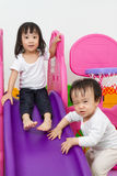Asian Chinese little sister and brother playing on the slide Stock Image