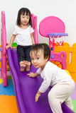Asian Chinese little sister and brother playing on the slide Royalty Free Stock Photography