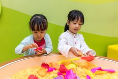 Asian Chinese Little Sister Playing Kinetic Sand. At Indoor Playground Royalty Free Stock Photo