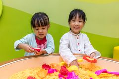 Asian Chinese Little Sister Playing Kinetic Sand. At Indoor Playground Stock Photo