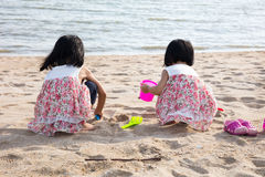 Asian Chinese little sister playing sand at seaside Royalty Free Stock Photos