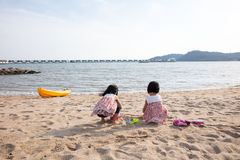 Asian Chinese little sister playing sand at seaside Stock Photo