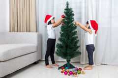 Asian Chinese little sisters decorating Christmas tree at home Royalty Free Stock Photos