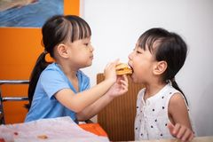 Asian Chinese little sisters eating burger. At indoor restaurant stock image