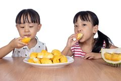 Asian Chinese little sisters eating durian fruit. In isolated white background stock photo