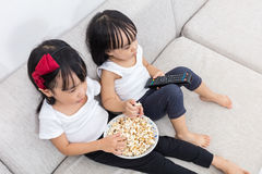 Asian Chinese little sisters eating popcorn on the sofa Royalty Free Stock Photos