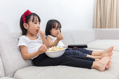 Asian Chinese little sisters eating popcorn on the sofa Royalty Free Stock Photography