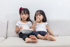 Asian Chinese little sisters eating popcorn on the sofa. In the living room at home Stock Photography