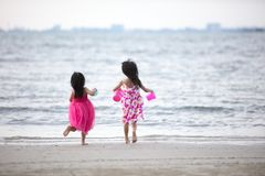 Asian Chinese little sisters having fun. At beach outdoor stock photography