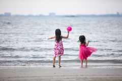 Asian Chinese little sisters having fun. At beach outdoor stock images