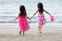 Asian Chinese little sisters having fun. At beach outdoor royalty free stock image