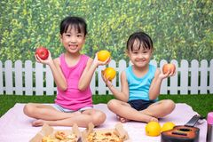 Asian Chinese little sisters having picnic. At outdoor garden stock photos
