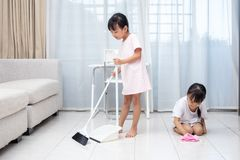 Asian Chinese little sisters helping doing cleaning. At home stock photos