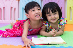 Asian Chinese little sisters laying on the floor reading. At home stock photos