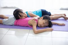 Asian Chinese little sisters lying on yoga mat. In the living room at home royalty free stock photography