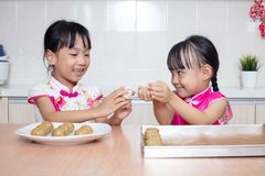 Asian Chinese little sisters making moon cake in the kitchen. At home stock photography