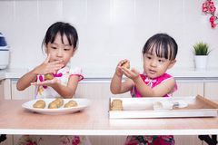 Asian Chinese little sisters making moon cake in the kitchen. At home royalty free stock photo