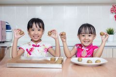 Asian Chinese little sisters making moon cake in the kitchen. At home royalty free stock images