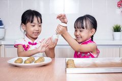 Asian Chinese little sisters making moon cake in the kitchen. At home stock image