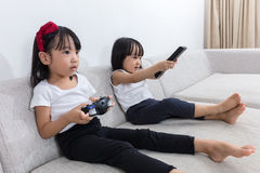 Asian Chinese little sisters playing TV games on the sofa Royalty Free Stock Photos