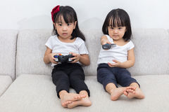 Asian Chinese little sisters playing TV games on the sofa Royalty Free Stock Photo