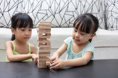 Asian Chinese little sisters playing wooden stacks. At home stock images