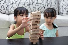 Asian Chinese little sisters playing wooden stacks. At home royalty free stock photos