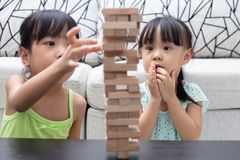 Asian Chinese little sisters playing wooden stacks. At home stock photography