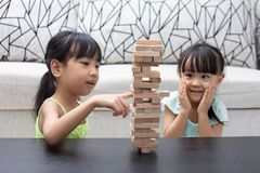 Asian Chinese little sisters playing wooden stacks. At home royalty free stock images