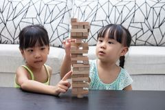 Asian Chinese little sisters playing wooden stacks. At home stock photos